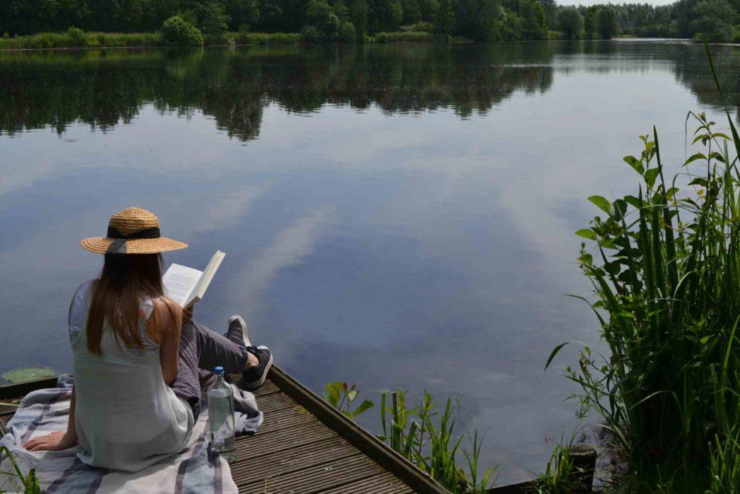 Frau sitzend auf Steg am Wasser